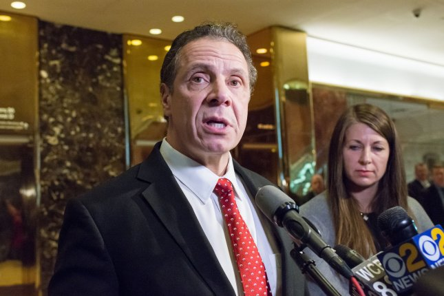 New York State Governor Andrew Cuomo speaks with reporters in the lobby of Trump Tower in New York City on January 18, 2017. On Wednesday, Cuomo said he plans to sue the federal government over tax legislation that he says is illegally burdens his state. Pool photo by Albin Lohr-Jones/Pool