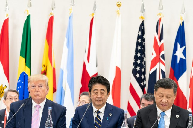 President Donald J. Trump, seated next to Japanese Prime Minister Shinzo Abe, listens as China's President Xi Jinping (right) delivers remarks at the G20 Leaders Special Event on the Digital Economy at the G20 Japan Summit on Saturday, in Osaka, Japan. Photo by Shealah Craighead/White House/UPI