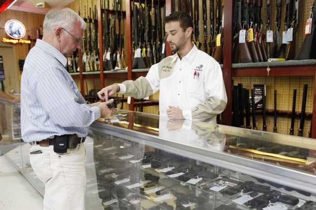 A man examines a handgun at a firearms shop in Dundee, Ill. The high court said Monday it refused to rule in the case because New York City did precisely what the plaintiffs asked for. File Photo by Brian Kersey/UPI