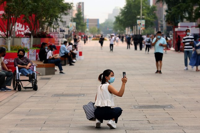 A Chinese woman takes photos of a nearly empty tourist shopping area as the coronavirus threat remains at level 2 in Beijing on Wednesday. Photo by Stephen Shaver/UPI
