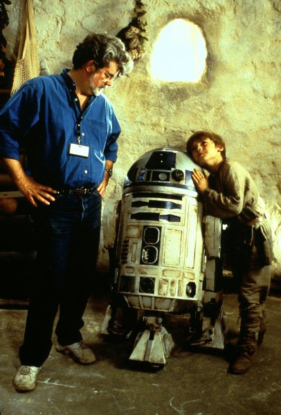 LAP99051519 - 15 MAY 1999 - LOS ANGELES, CALIFORNIA, USA: Director George Lucas shares his thoughts with droid R2-D2 and actor Jake Lloyd, who plays young Anakin Skywalker, on the set of the Skywalker hovel for Star Wars: Episode I The Phantom Menace. The first prequel to the long-anticipated motion picture opens nationwide Wednesday, May 19 in the USA for millions of fans, some of whom waited in line several weeks for tickets. jr/Keith Hamshere/Lucasfilm UPI
