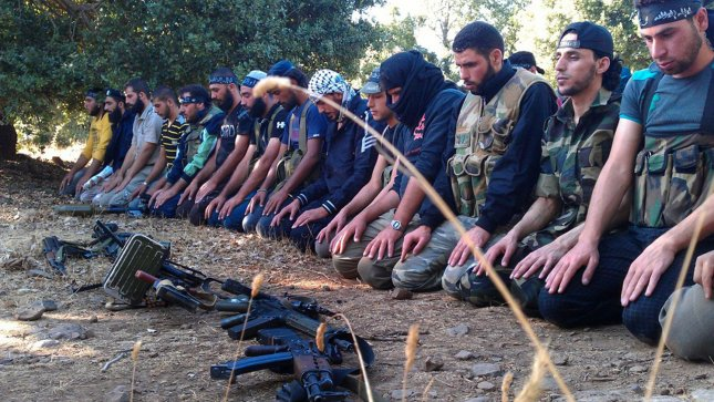 Members of the Free Syrian Army perform prayers in Damascus. U.S. support for the rebel forces may include a no-fly zone which would extend as many as 25 miles into Syria from Jordan FILE/UPI
