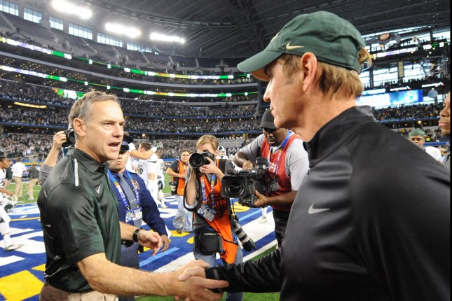 Michigan State head coach Mark Dantonio, left, shakes hands with former Baylor Bears head coach Art Briles after the Spartans beat the Bears 42-41 in the Goodyear Cotton Bowl Class in AT&T Stadium, Arlington, Texas on January 1, 2015. Ian Halperin/UPI