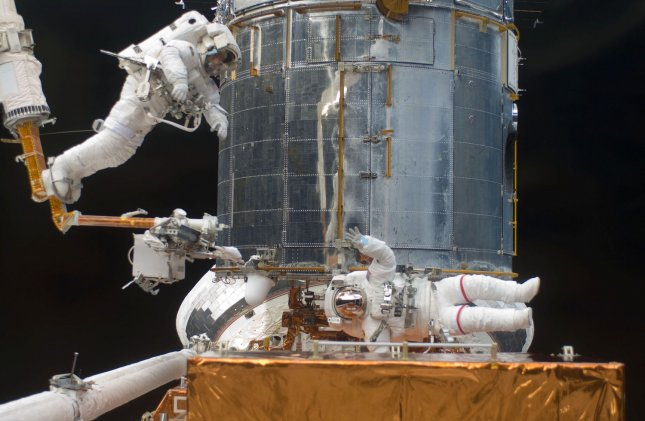 This NASA photo shows astronaut Andrew Feustel, STS-125 mission specialist, as he navigates near the Hubble Space Telescope on the end of the remote manipulator system arm, controlled from inside Atlantis' crew cabin, May 16, 2009. Astronaut John Grunsfeld signals to his crewmate from just a few feet away. Astronauts Feustel and Grunsfeld were continuing servicing work on the giant observatory, locked down in the cargo bay of the shuttle. (UPI Photo/NASA)