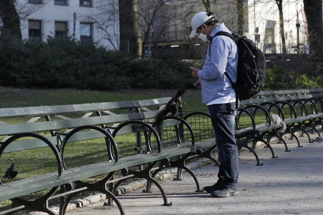 A man wearing a protective face mask feeds squirrels surrounded by empty benches in an uncrowded Central Park in New York City in March 2020. File Photo by John Angelillo/UPI