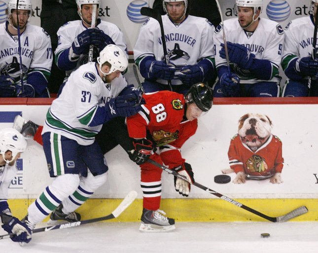 Vancouver Canucks center Rick Rypien (L) checks Chicago Blackhawks right wing Patrick Kane into the boards at the United Center in Chicago, May 11, 2009. (UPI Photo/Brian Kersey)
