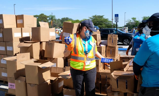 A volunteer wearing a mask is shown at a drive-thru food distribution event sponsored by Feeding South Florida of Boynton Beach at the Boynton Beach mall parking lot. File Photo By Gary I Rothstein/UPI