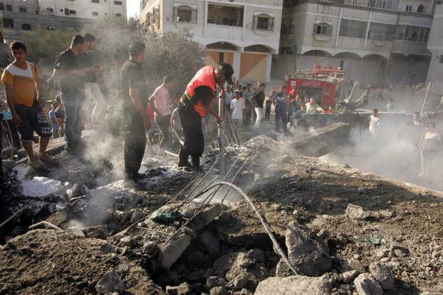 A Palestinian firefighter extinguishes a fire after renewed air strikes on Rafah in the southern part of the Gaza Strip on August 20, 2014. Truce talks failed in Cairo, with Israel apparently targeting the Hamas military chief, killing his wife and child. UPI/Ismael Mohamad