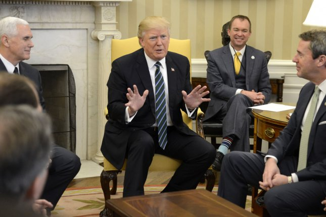 President Donald Trump (C) makes remarks and Vice President Mike Pence (L) listens as they meet with the House Republican Study Committee in the Oval Office of the White House on Friday. Rep. Mark Walker, R-N.C., heads the committee. Photo by Mike Theiler/UPI