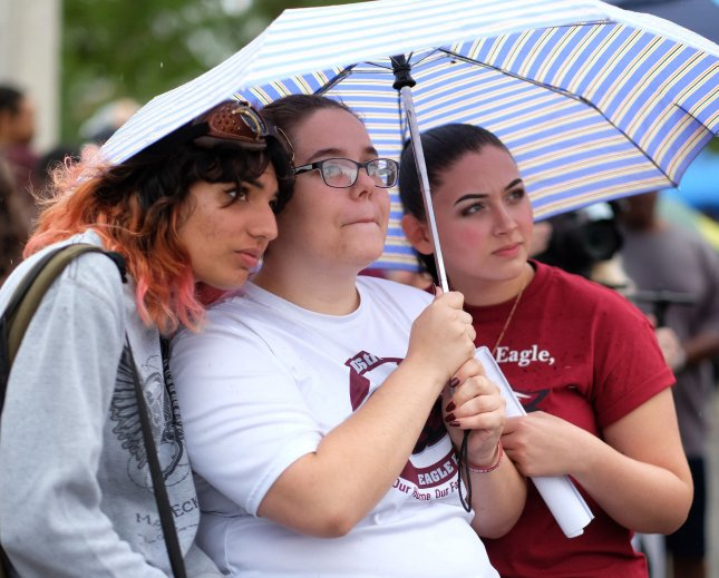 Students (L-R) Scharon Specht, Sarah Cumings and Angelina Lazo all seniors at Marjory Stoneman Douglas High School listen to speakers at a rally for solidarity in North Community Park, Coral Springs, Florida on Saturday. Photo by Gary Rothstein/UPI