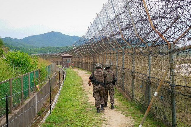 Soldiers walk alongside a barbed wire fence in the DMZ on a trail in Goseong. File Photo by Thomas Maresca/UPI
