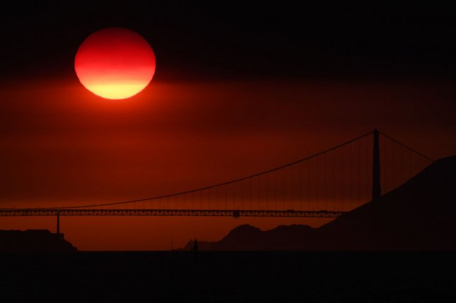 The sun descends behind the Golden Gate Bridge, through smoke and haze from a nearby wildfire in 2017, as seen from Emeryville, Calif. File Photo by Terry Schmitt/UPI