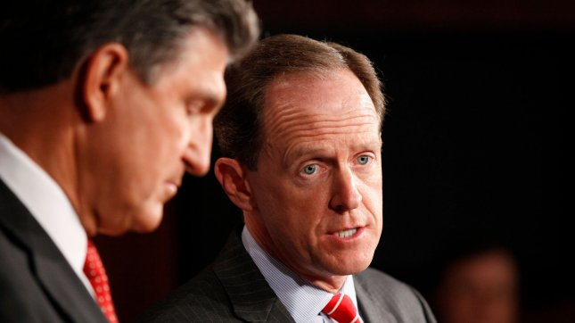 Senator Pat Toomey (R-PA), left, listens while Senator Joe Manchin (D-WV) speaks during a press conference to discuss expanding background checks for firearms, in Washington DC on April 10, 2013. UPI/Molly Riley