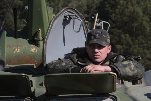 Ukrainian soldier sits in a tank during a military exercise. UPI/Sergey Starostenko