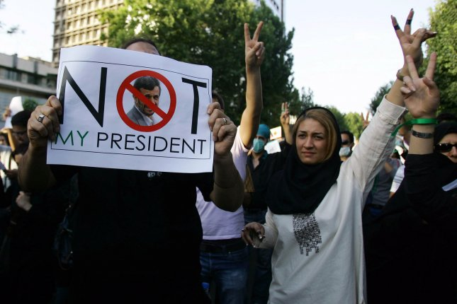 Supporters of reformist candidate Mir Hossein Mousavi hold an anti-Mahmoud Ahmadinejad placard as they gather on the streets of Tehran, Iran to demonstrate against the results of the Iranian presidential election on June 17, 2009. (UPI Photo)