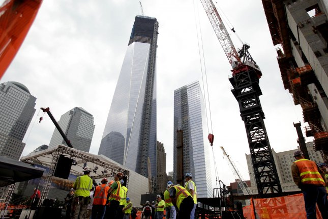 One world Trade center stands above construction workers at a topping out ceremony before the final steel beam is raised by crane to the top of Four World Trade Center in New York City on June 25, 2012. UPI/John Angelillo