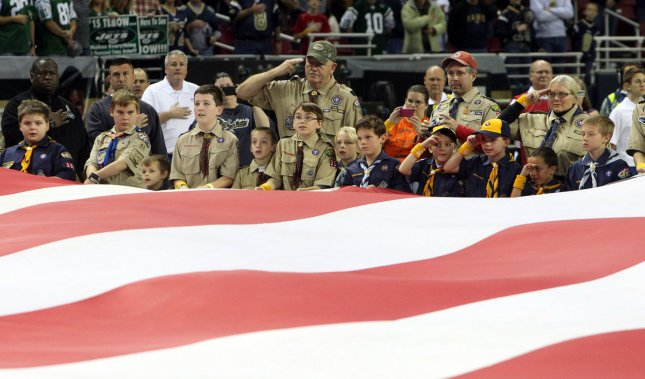 Boy Scouts and Cub Scouts hold an oversized American flag during ceremonies honoring veterans before a pro football game in St. Louis Nov. 18, 2012. UPI/Bill Greenblatt