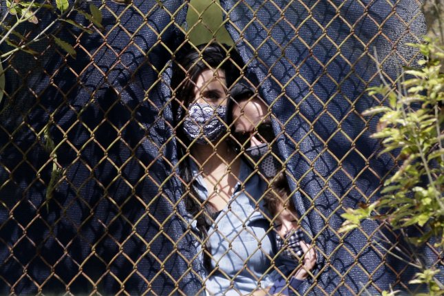 Fans peek through a chain link fence during the second round of the 102nd PGA Championship at TPC Harding Park in San Francisco, Calif., on Friday. Photo by John Angelillo/UPI