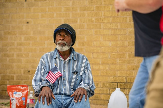 A homeless man holds an American flag near the Bank of Oklahoma Center in Tulsa, Okla., on June 20. File Photo by Kyle Rivas/UPI