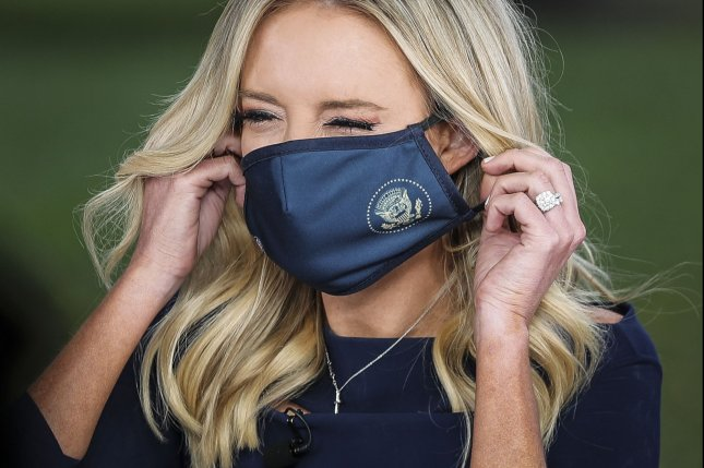 White House press secretary Kayleigh McEnany puts on a mask on after talking to reporters Friday outside the West Wing of the White House in Washington, D.C. Photo by Oliver Contreras/UPI