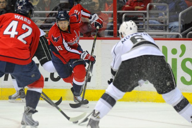 Washington Capitals right wing Eric Fehr (16) passes the puck against Los Angeles Kings defenseman Jake Muzzin (6) in the first period at the Verizon Center in Washington, D.C. on March 25, 2014. UPI/Mark Goldman