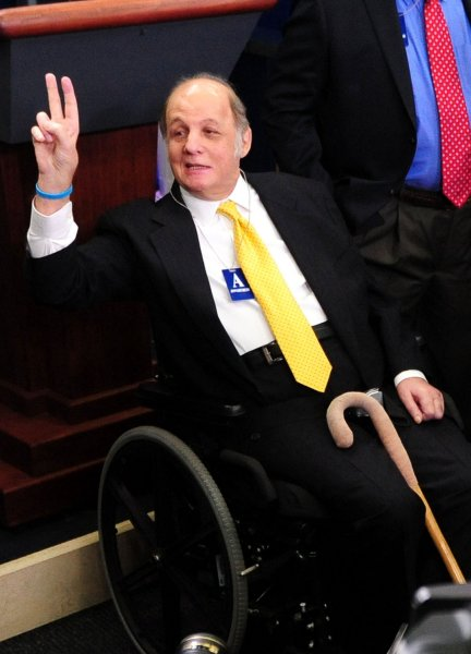 Former White House press secretary James Brady (C), who was paralyzed during the assassination attempt on President Ronald Reagan, makes the peace sign as he speaks to members of the press as he visits the White House on the 30th anniversary of the assassination attempt, in Washington, March 30, 2011. UPI/Kevin Dietsch