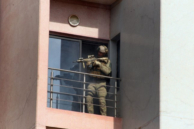A member of Mali special forces stand outside balcony of the Radisson Blu hotel in Bamako on Friday. Gunmen with grenades stormed into the hotel early Friday, firing automatic weapons and seizing more than 100 guests and staff in a hostage-taking siege that left more than two dozen people dead, according to authorities. photo by Hapep/ UPI