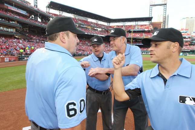 Umpires give home plate umpire Marty Foster a punch to the chest protector for good luck before the start of a game. Photo by Bill Greenblatt/UPI