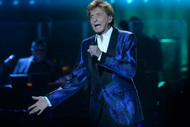 Barry Manilow shows off his wedding ring during his performance at Staples Center in Los Angeles on April 14, 2015. The singer is now doing well, according to his publicist, following his recent emergency surgery. File Photo by Jim Ruymen/UPI