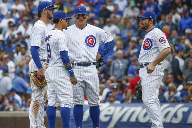 Chicago Cubs third baseman Kris Bryant (17), shortstop Javier Baez (9), first baseman Anthony Rizzo (44) and second baseman Daniel Murphy (3) talk to each other in the eighth inning of a National League tiebreaker baseball game against the Milwaukee Brewers on October 1 at Wrigley Field in Chicago. Photo by Kamil Krzaczynski/UPI