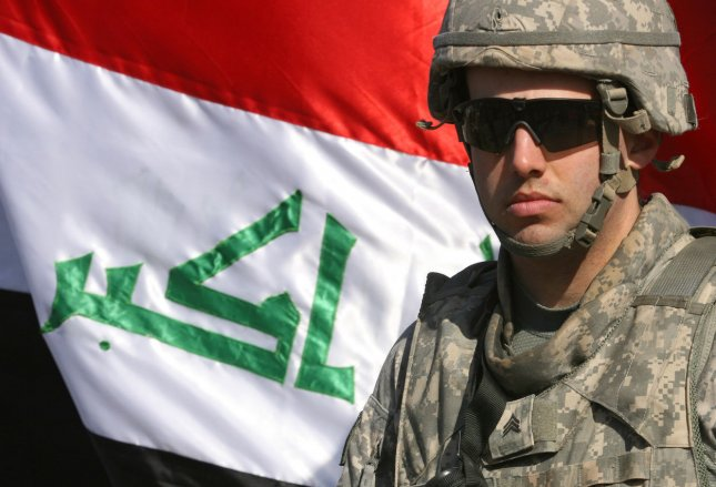 A U.S. soldier stands guard near an Iraqi flag during a handover ceremony of the Green Zone to Iraqi authorities in Baghdad on January 1, 2009. Iraqi President Nouri al-Maliki said the handover symbolized the restoration of Iraqi sovereignty. (UPI photo/Ali Jasim)