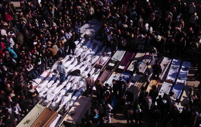 Syrian mourners gather around the bodies of people allegedly killed by Syrian government forces during a funeral procession in Maarat al-Noman, Idlib province, Syria, February 7, 2012. UPI