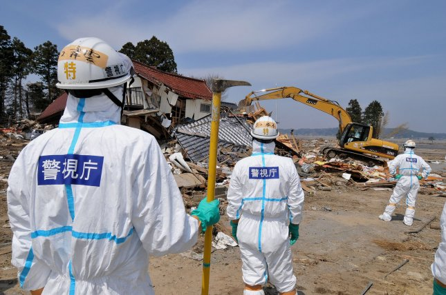 Japanese police wearing chemical protection suits search for victims inside the 12-mile radius around the Fukushima Dai-ichi nuclear power plant in Minamisoma, Fukushima prefecture, Japan, in April 2011. UPI/Keizo Mori