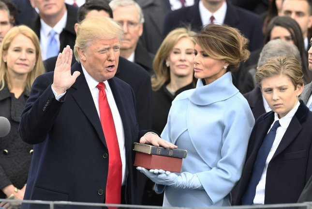 Then President-elect Donald Trump, accompanied by his wife Melania and son Barron, places his hand on two Bibles as he is sworn in during his inauguration at the Capitol on January 20, 2017, in Washington, D.C. File Photo by Mike Theiler/UPI