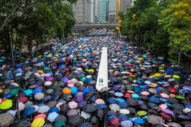 A large crowd of protesters under umbrellas leave an anti-government rally in Hong Kong's Victoria Park on August 18. Photo by Thomas Maresca/UPI
