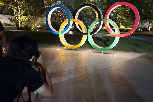 Visitors take photos of the Olympic Rings at the National Stadium in Tokyo, Japan, on Friday. The 2020 Summer Games are scheduled to begin in July 2021. Photo by Keizo Mori/UPI