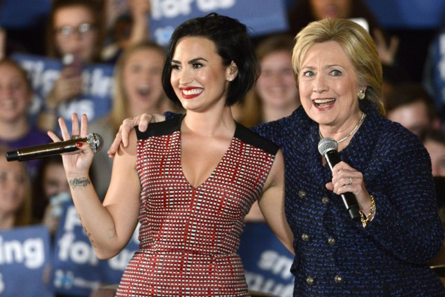 Hillary Clinton (R) embraces singer Demi Lovato as she arrives onstage during a campaign event at University of Iowa on Thursday in Iowa City, Iowa. Photo by Mike Theiler/UPI