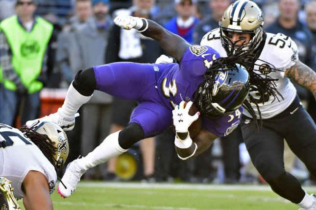 Baltimore Ravens running back Alex Collins (34) drives for yardage in front of New Orleans Saints linebacker A.J. Klein (53) during the first half of an NFL game on October 21 at M&T Bank Stadium in Baltimore. Photo by David Tulis/UPI