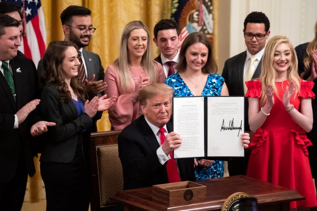 President Donald Trump holds up a copy of an executive order on improving free inquiry, transparency, and accountability on campus during a signing ceremony at the White House in Washington, D.C. on Thursday. Photo by Kevin Dietsch/UPI