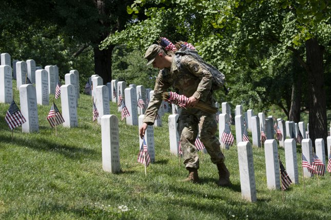 Old Guard soldiers place American flags at the tombstones of the fallen at Arlington National Cemetery. Photo by Pat Benic/UPI