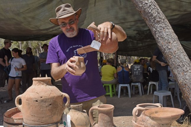Professor Yosef Garfinkel, head of the Institute of Archeology at the Hebrew University, examines 3,000-year-old pottery vessels found at the site believed to be the biblical town of Ziklag, near the Israeli southern city of Kiryat Gat, Israel, Monday. Photo by Debbie Hill/UPI