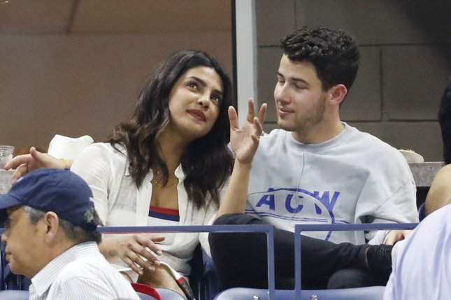 Nick Jonas (R) and Priyanka Chopra watch Dominic Thiem the 2018 U.S. Open Tennis Championships in New York City. On Sunday, in North Carolina, they celebrated their marriage. File photo by John Angelillo/UPI