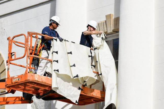 Workers attach hurricane cloth to the historic Federal Court House in preparation for Hurricane Dorian on September 2 in Charleston, S.C. South Carolina reached an all-time unemployment low in September. File Photo by Richard Ellis/UPI