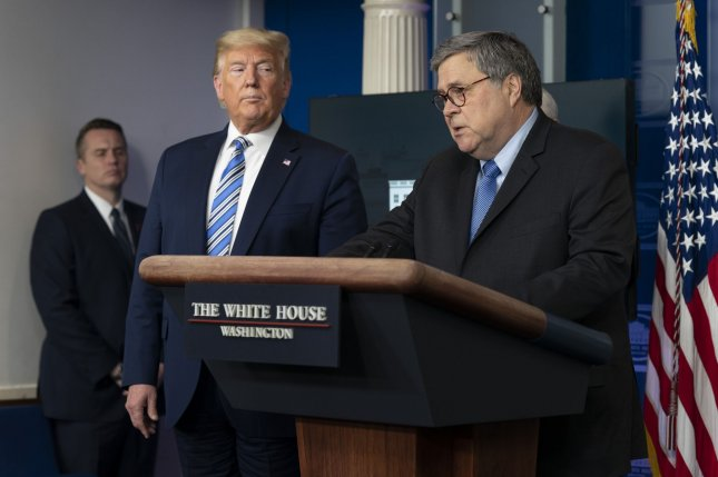 U.S. Attorney General William Barr speaks to reporters at the White House on March 23, as President Donald Trump looks on. Photo by Chris Kleponis/UPI