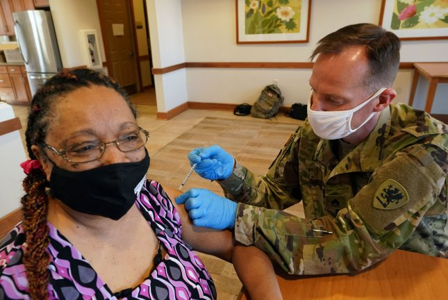 The Pentagon announced more troops -- like Missouri National Guardsman Herbert Lin, pictured injecting Patricia Bolden with a COVID-19 vaccine in St. Louis on March 4 -- will be deployed to vaccinate civilian populations across the United States. File Photo by Bill Greenblatt/UPI