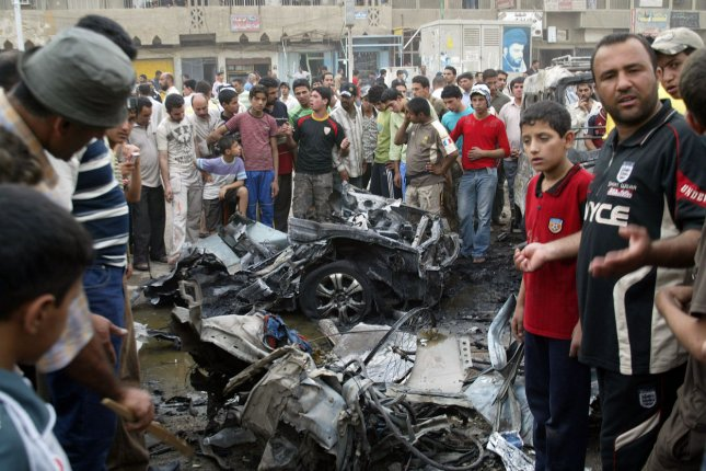 People gather around a vehicle destroyed in a car bomb blast in Baghdad's Shiite enclave of Sadr City, Iraq, on April 30, 2009. (UPI Photo/Ali Jasim)