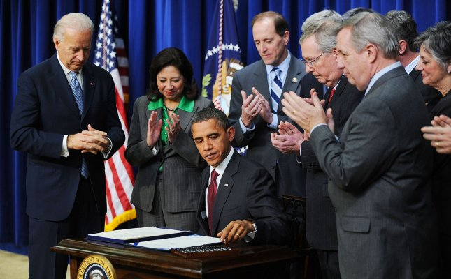 President Barack Obama, flanked by Vice President Biden and members of Congress including Senate Minority Leader Mitch Mc Connell, signs the middle-class tax cut bill in the Eisenhower Executive Office Building on December 17, 2010 in Washington DC. The measure would extend tax cuts for families at every income level, renew jobless benefits for the long-term unemployed and enact a new one-year cut in Social Security taxes that would benefit nearly every worker who earns a wage. UPI/Olivier Douliery/POOL