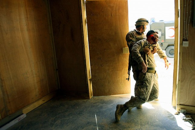 An Iraqi soldier drags a mock casualty, role-played by Hospitalman James J. Campbell, a U.S. Navy Corpsman with Regimental Combat Team 7, out of a wooden hut and to safety during a mass casualty drill March 19, 2006, at the Iraqi Army camp at Al Asad, Iraq. performance. (Photo by Staff Sgt. Jim Goodwin)