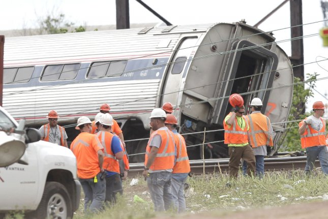 Workers surround a car of an Amtrak train that crashed Tuesday night near Philadelphia. All seven cars of Amtrak Northeast Regional Train 188 derailed near Frankford Junction. Photo by John Angelillo/UPI