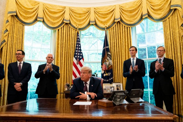 President Donald Trump listens to applause in the Oval Office after the announcement that Bahrain will normalize relations with Israel on Friday. Vice President Mike Pence and senior adviser Jared Kushner are in the background. Pool Photo by Anna Moneymaker/UPI